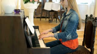 Stylish girl playing the piano and smiling to the camera, steadycam shot