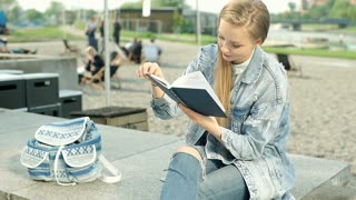 Stylish girl sitting in the public place and reading a book, steadycam shot