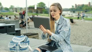 Stylish girl using tablet and connects screen to laptop outdoors
