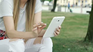 Stylish girl with ripped jeans sitting in the park and using tablet, steadycam s