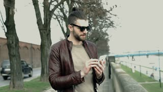 Stylish man in leather jacket using smartphone while standing on boulevards