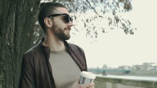 Stylish man leaning on the tree and drinking coffee on boulevards