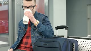 Stylish man relaxing on the train station and drinking coffee to go, steadycam s