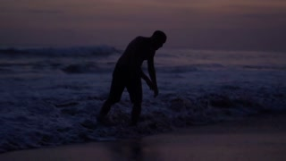 Tired man crawling on the beach, steadycam shot, slow motion shot at 240fps
