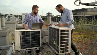 Two men working on the air condition while standing on the roof, steadycam shot