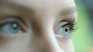 View of girl's beautiful blue eyes which are moving in all directions