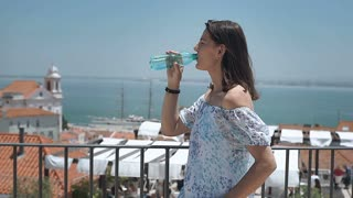 Woman drinking water on the balcony with view on the sea and smiling to the came