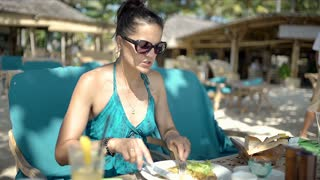 Woman eating lunch on the beach and talking with her son, steadycam shot