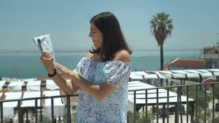 Woman feels very hot and cools herself down with a map, steadycam shot