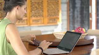 Woman finish using laptop in the dining room and stretching hands, steadycam sho