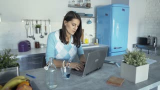 Woman finishes working on computer in the kitchen and looks satisfied, steadycam