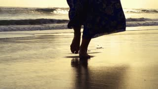 Woman in dress walking on the sandy beach, steadycam shot, slow motion shot at 2
