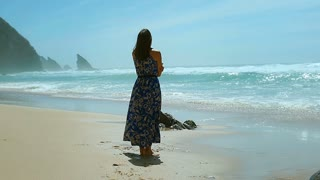 Woman in flowy dress standing on the sandy beach next to the seaside, steadycam