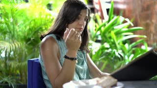 Woman looks dissatisfied while reading menu in exotic restaurant, steadycam shot