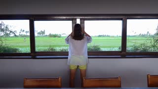 Woman opens window and enjoys the view, slow motion shot at 240fps, steadycam sh