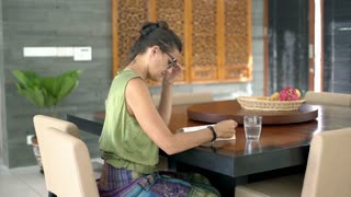 Woman reading funny book while sitting in the dining room, steadycam shot