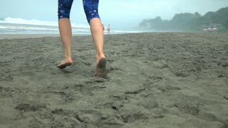 Woman running barefoot on the sandy beach, slow motion shot at 240fps, steadycam