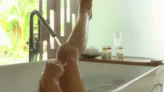 Woman shaving her leg while having a bath, steadycam shot, slow motion shot at 2