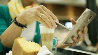 Woman sitting in the cafe and browsing internet on smartphone, steadycam shot