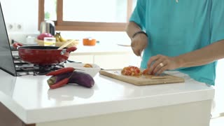 Woman standing in the kitchen and cooking dinner, steadycam shot