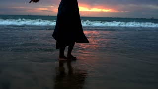 Woman standing in the sea at the evening and feels free, steadycam shot
