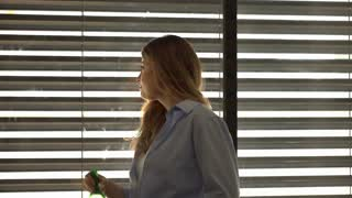 Woman standing next to the window and drinking water from bottle, steadycam shot