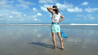 Woman standing on the beach and relaxing, slow motion shot at 240fps, steadycam