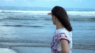 Woman standing on the windy beach and looking around, slow motion shot at 240fps