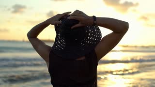 Woman takes off straw hat and admires sunset while standing next to the sea, ste