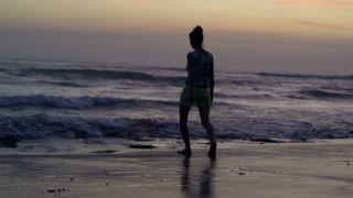 Woman walking on the beach at the evening, steadycam shot, slow motion shot at 2