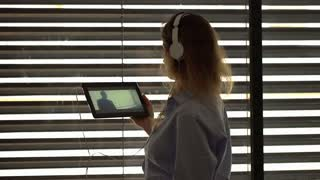 Woman wearing headphones and watching movie on tablet in the flat