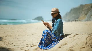 Woman wearing protection from sun and looking for signal on mobile phone