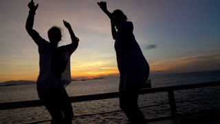 Women dancing next to the sea and feel joy, slow motion shot at 240fps, steadyca
