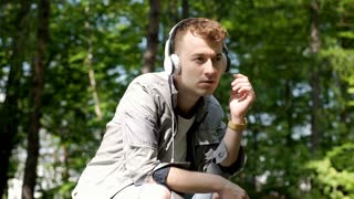 Worried boy sitting in the park and listening music on headphones, steadycam sho