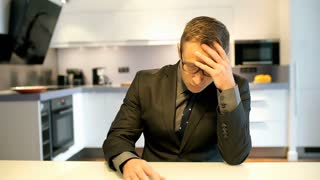 Worried businessman sitting in the kitchen and looking to the camera