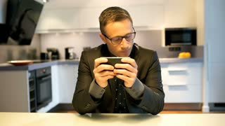 Worried businessman sitting in the kitchen and texting on smartphone