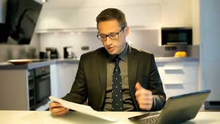 Worried businessman working on papers and laptop in the kitchen