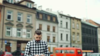Worried man in checked shirt walking on the square and looks lost