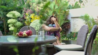 Worried woman sitting in her exotic garden and thinking about problems, steadyca