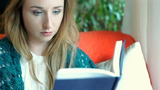 Young girl crying while reading very sad book, steadycam shot