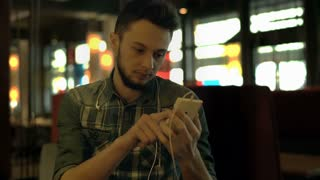 Young man drinking coffee in the dark cafe and browsing internet on smartphone