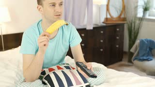 Young man eating banana and watching television while sitting in bed, steadycam