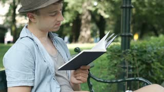 Young man in hat reading interesting book in the park, steadycam shot