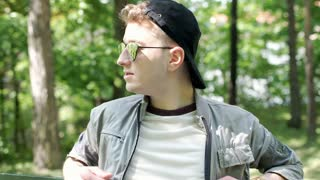 Young man in stylish sunglasses sitting in the park and relaxing, steadycam shot