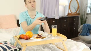 Young man looks bored while watching tv and eating breakfast in bed, steadycam s