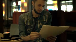 Young man receives message on smartphone while reading notes in the dark cafe, s