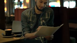 Young man sitting in the dark cafe and studying from notes, steadycam shot