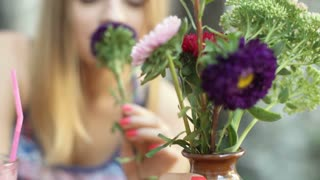 View of bunch of colorful flowers being smelled by girl