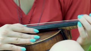 View of female hands touching strings while playing on violin, steadycam shor