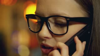 View of girl wearing glasses and talking on cellphone, steadycam shot